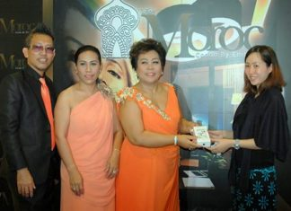 Sukanya Klayhong (center), Executive Manager of the Moroc Condo project, presents an iPhone 5 to a customer who registered on the official launch day, Oct. 20.