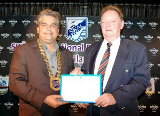 President Tony Malhotra presents a membership certificate to Allan Riddell, director of SATCC.