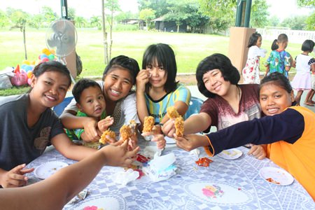 Children showing off their favorite chicken wings distributed by Hilton Hotel, Pattaya, for lunch at Child Protection and Development Center.