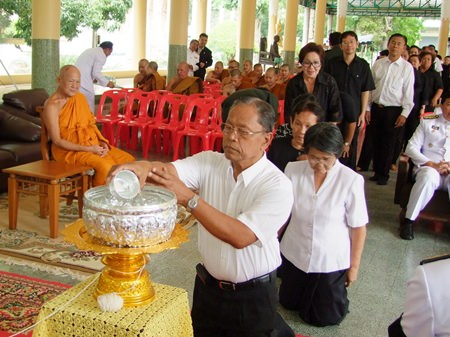 Phra Thep Suttajan, head of the province's monk committee and abbot of Khao Bangsrai Temple (left) looks on as mourners take part in the water-ablution ceremony for the former Supreme Patriarch.