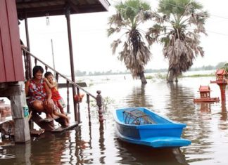 Auk Pansaa, the end of Buddhist Lent, in theory signals the end of the rainy season in Thailand. This cannot come too soon for some families in the region, as shown by this mother and child, smiling in the face of adversity from the steps of their flooded home in Prachinburi, waiting patiently for relief aid from local authorities.