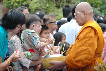 The Tak Bat Devo ceremony is another tradition that families can do good by making merit together.