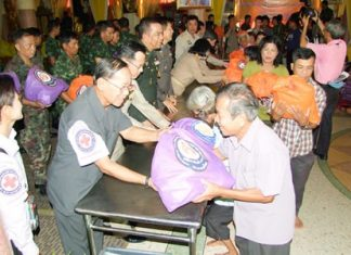 Civil servants, police and military personnel hand out bags of relief supplies from HRH Princess Soamsawalee's Princess Pa Foundation for victims of flooding in Phanat Nikhom.