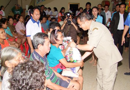 Deputy Interior Minister Visarn Techateerawat hands out bags of flood relief supplies to residents of Panthong.