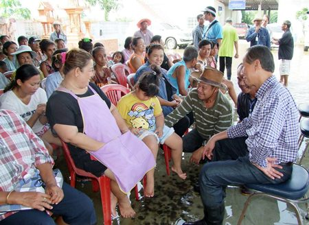 Chonburi Gov. Khomsan Ekachai (seated right) meets with local residents whilst sitting in flood waters during his tour of the province.