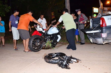 Police and rescue workers remove what is left of the motorcycle.