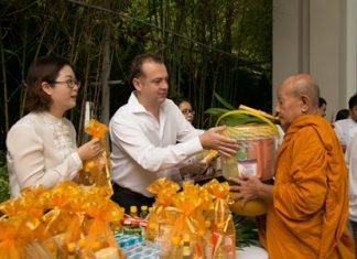 Garth Solly, GM of Holiday Inn Pattaya presents alms to revered monk.