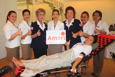 Latiporn Tongkhunna (center), executive assistant manager of Amari Orchid Pattaya, with employees and members of Banglamung Red Cross give thumbs up to donating blood for the Queen Savang Vadhana Hospital.