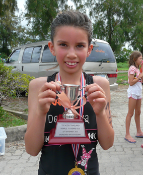 8-year old Sarah-Michelle Clear poses with her trophy after completing the Tri Kids Triathlon in Bangkok, Sunday, Sept. 15.
