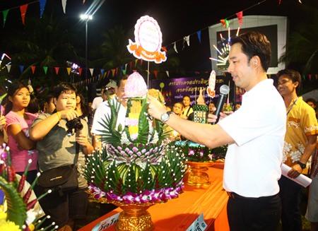Mayor Itthiphol Kunplome plants the winning flag onto Wat Photisampan 1 team's krathong, the winner of krathong contest at the elementary school level.