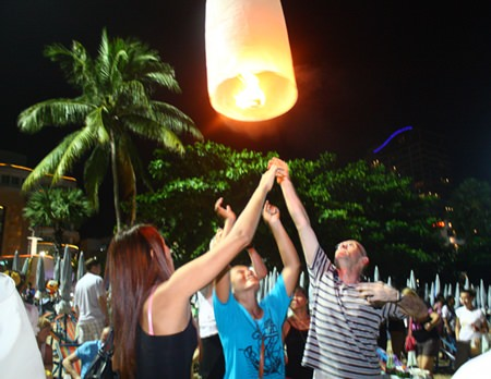 Tourists launch a khomloy into the air for good luck on Pattaya Beach.