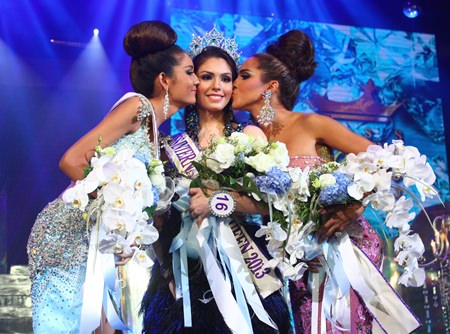Second runner-up Netnapada Kanlayanon (left) and First runner-up American Shantell D'Marco (right) kiss Marcelo Ohio (central) on the cheek after Ohio won the Miss International Queen 2013 contest.