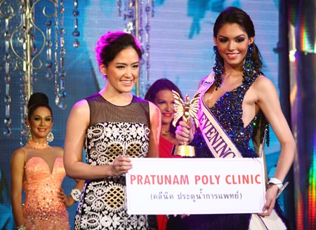 Alisa Phanthusak (left), Assistant Managing Director of Tiffany's Show Pattaya Co., Ltd., presents the Best Evening Gown award to Marcelo Ohio (right).