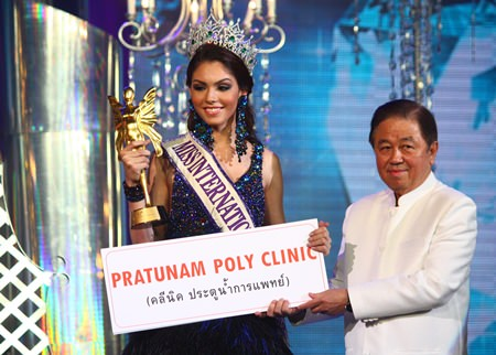 Senator Sutham Phanthusak (right), Managing Director of Tiffany's Show Pattaya Co., Ltd., presents the top award to Miss International Queen 2013 Marcelo Ohio.