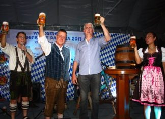"""Their beer krugs charged to the brim, Brendan, Ken and Panpicha cry """"Prost""""."""