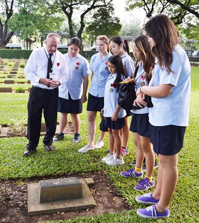 GIS students stand by a grave at the War Cemetery in Kanchanaburi.