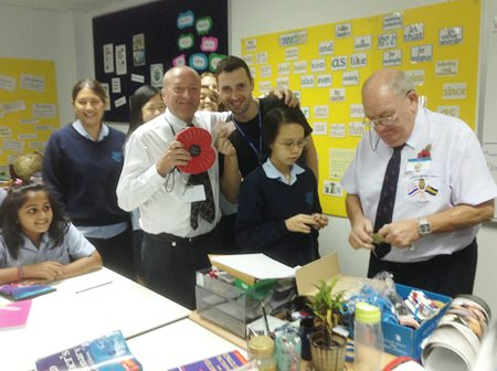 A Royal British Legion volunteer sells poppies to GIS students.
