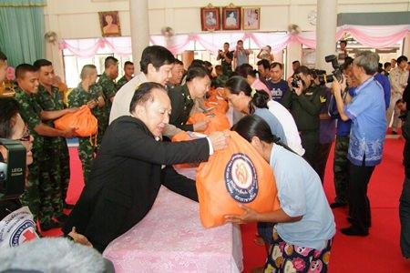 Rajawongse Somlap Kittiyakorn, secretary to HRH Princess Soamsawalee presents disaster relief bags to Panthong residents at Khok Kheenon Temple.