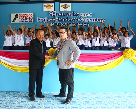 Children show off the rock 'n' roll symbol to thank Jorge Carlos Smith (right), General Manager of Hard Rock Hotel Pattaya & Hard Rock Cafe Pattaya, shown here shaking hands with Viroj Ampornvichai (left), director of Huay Yai School, during the presentation of the new canteen.