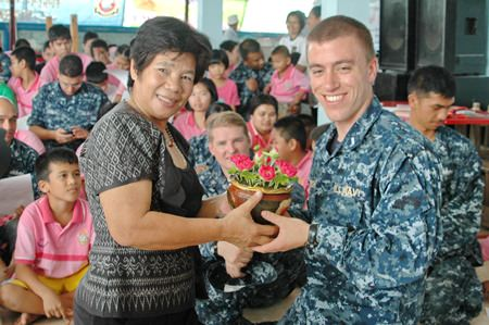 Teacher Boonchu Muangmaitong (left) presents a thank you gift to a representative of the USS Mustin Crew.