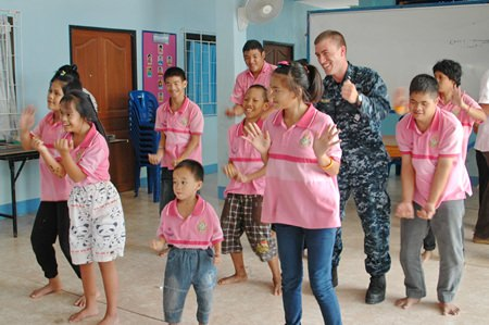 Everyone is having a great time when sailors from the USS Mustin dance with the children.