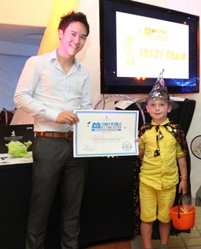 "Executive Director of Royal Cliff Hotels Group, Vitanart Vathanakul, presents a certificate and special pumpkin loot bag for ""Best Halloween Costume"" to Sava ""the little wizard""."