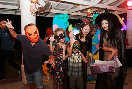 "Maria Gequillana, PR and Marcom Manager of Royal Cliff Hotels Group with charming masked visitors at the ""Monsters at the Cliff"" Halloween Family Fun."