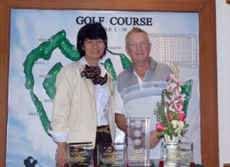Bob Pearce (right) poses for a photo with Jintana Poonchai (left) of the Pattaya Country Club management team. In front of Bob are his three individual hole-in-one trophies plus the unique 'ball tower'.