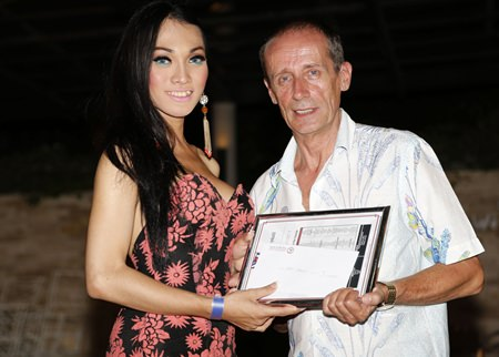 Miss Indonesia (left) presents a check for 250,000 baht to Jim Howard Smith of Phuket who accepts it on behalf of The Life Home Project.