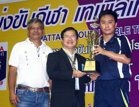 Jamlong Passara (left), former president, and Father Pichan Jaiseri (center), president of Rotary Pattaya, present the winning award to U-18 champion Khamron Hiranyasiri from the Pattaya Sports Club.