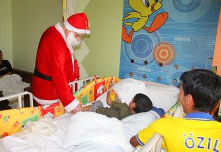 Santa Claus visits a young patient at Bangkok Hospital Pattaya to give him some gifts and lift his spirits.