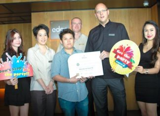 Hilton Pattaya GM Rudolf Troestler (2nd right) presents the grand prize to Ornchuma Watanakorn (front row, 3rd left) as Hilton management and staff help her to celebrate.