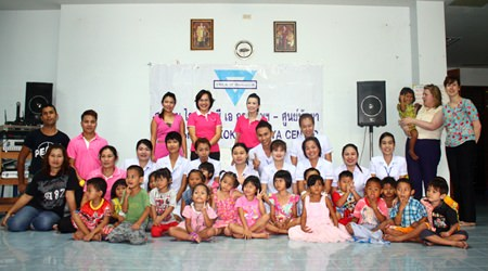YWCA Chairwoman Praichit Jetpai (back, right), along with nursing students from Chonburi Health Care School, staff of Nisha Clinic and the Jutamat Beauty School organized free checkups and haircuts for children at the Fountain of Life Center