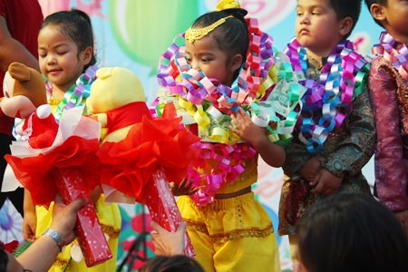 Parents present gifts to their children after their children's stage performance on Children's Day at Wat Chaimongkol Children's Development Center.
