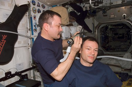 Cosmonaut Mikhail Tyurin, trims commander Michael E. Lopez-Alegria's hair in the Unity node of the International Space Station. Tyurin used hair clippers fashioned with a vacuum device to garner freshly cut hair.