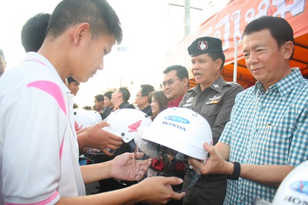Banglamung District Chief Sakchai Taengho (right), along with Col. Col. Supachai Phuikaewkhum (2nd right) distribute motorcycle helmets to students.