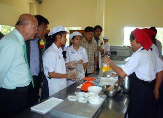 Deputy Mayor Wattana Chantanawaranon (left) looks on as students learn how to bake in the school's bakery-training facility.