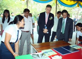 H.E. Enno Drofenik (center), Ambassador Extraordinary and Plenipotentiary of the Republic of Austria, and Watcharin Siriphanit (right), director of the Thai - Austria Technical College, listen to students presenting their inventions.