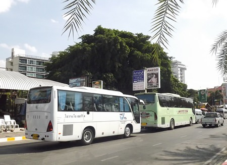Huge tour buses are seen double parking along Beach Road.