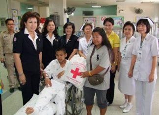 Chonburi Red Cross President Busarawadee Ekachai (left) presents cash and supplies to young hero, Sumet Kulprasart and his mother.
