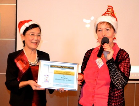 PCEC Treasurer Judith presents Toy with a Certificate of Appreciation from PCEC for her work for the Pattaya Orphanage, and for the inspiring presentation by the children.