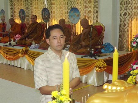 Mayor Itthiphol Kunplome lights candles during the auspicious ceremony.