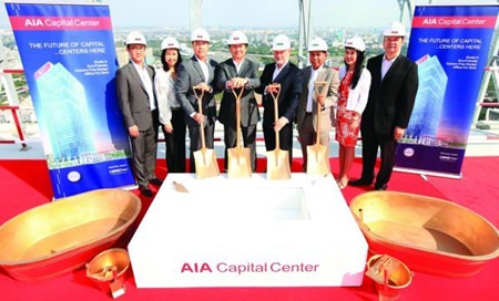 AIA executives pose for a photo on the roof of the AIA Capital Center in Bangkok during the building's topping out ceremony.