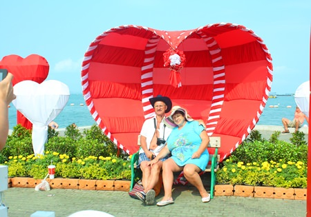 A Russian couple poses for a commemorative Valentine's photo at Pattaya Beach.