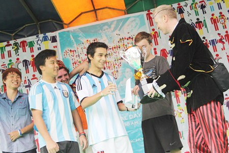 Principal Mike Walton hands over the Football World Cup Trophy to Team Argentina.
