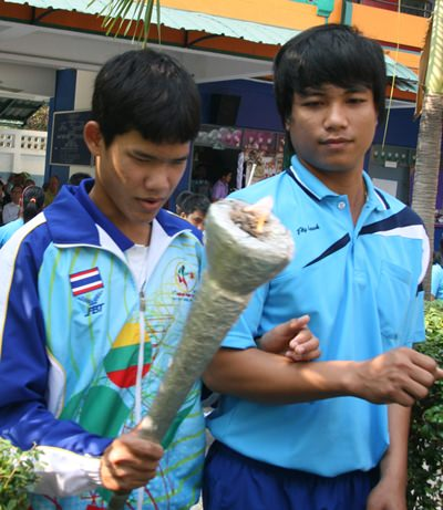 A student prepares to light the flame to open the games.