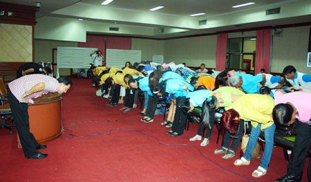 Mayor Itthiphol Kunplome (left) leads guests in some pre-meeting exercises.