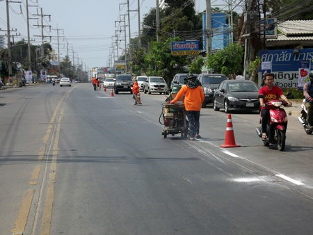 City workers repaint dividing lines on Thepprasit Road, the beginning of a citywide repainting project.