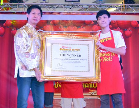 Somporn Naksuetrong (left), manager of Ripley's Pattaya, presents the winning plaque to Akharin Jatuporn.