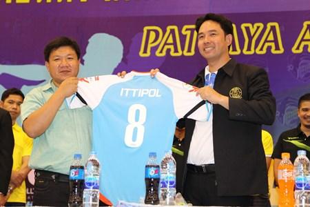 Nipitchon Ketpongpat, president of Pattaya Arena Futsal Club (left) presents a Pattaya Arena jersey to mayor Ittipol Kunplome at the press conference to launch the new Futsal team, held Tuesday, Feb. 18 at the Indoor stadium in Soi Chaiyapruek 2.